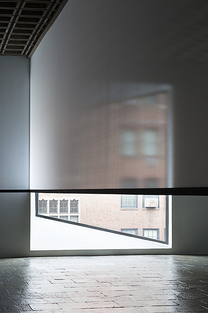 A gallery window with the shade partially open.