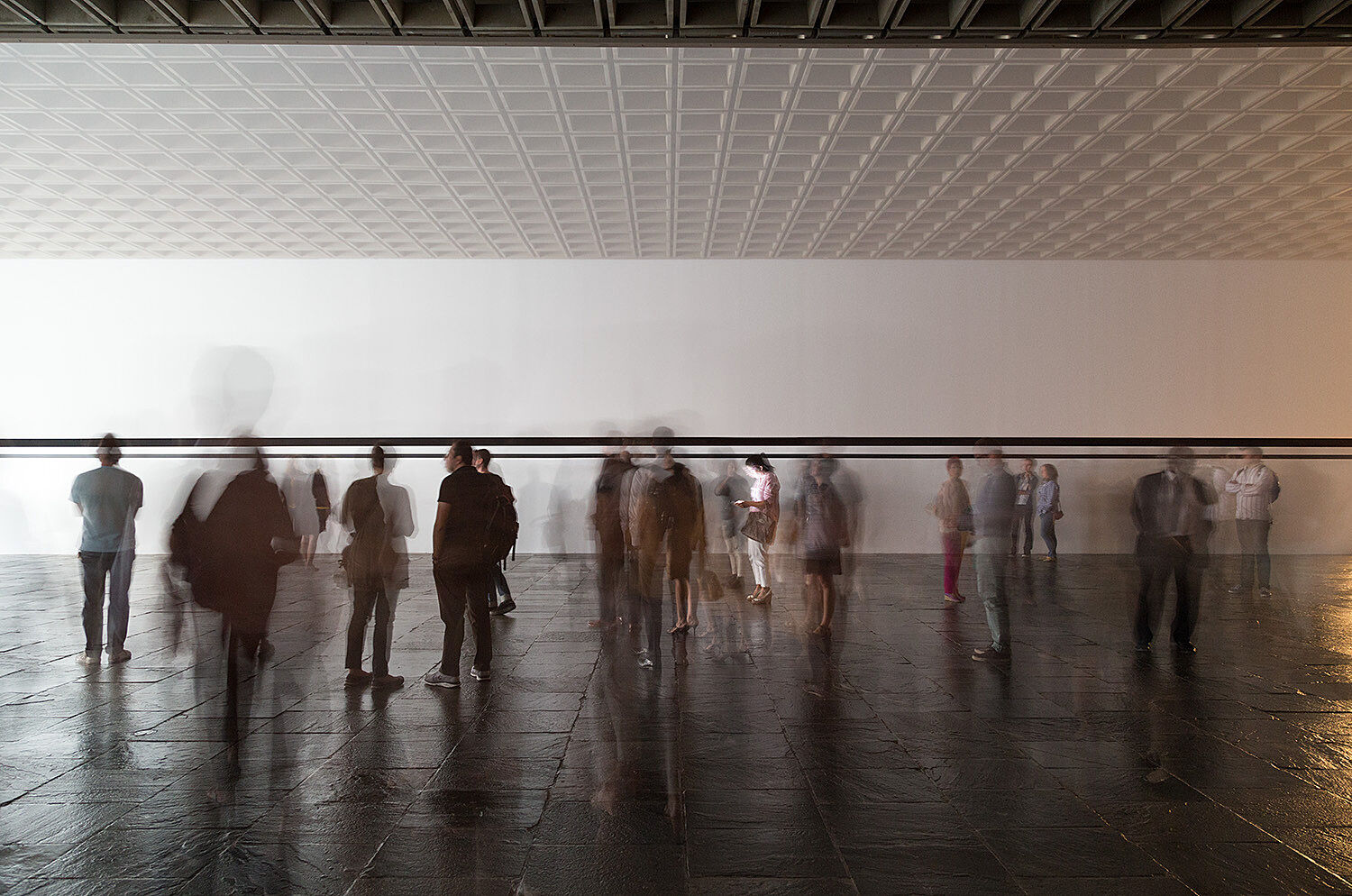 Blurred outlines of people standing in a gallery.