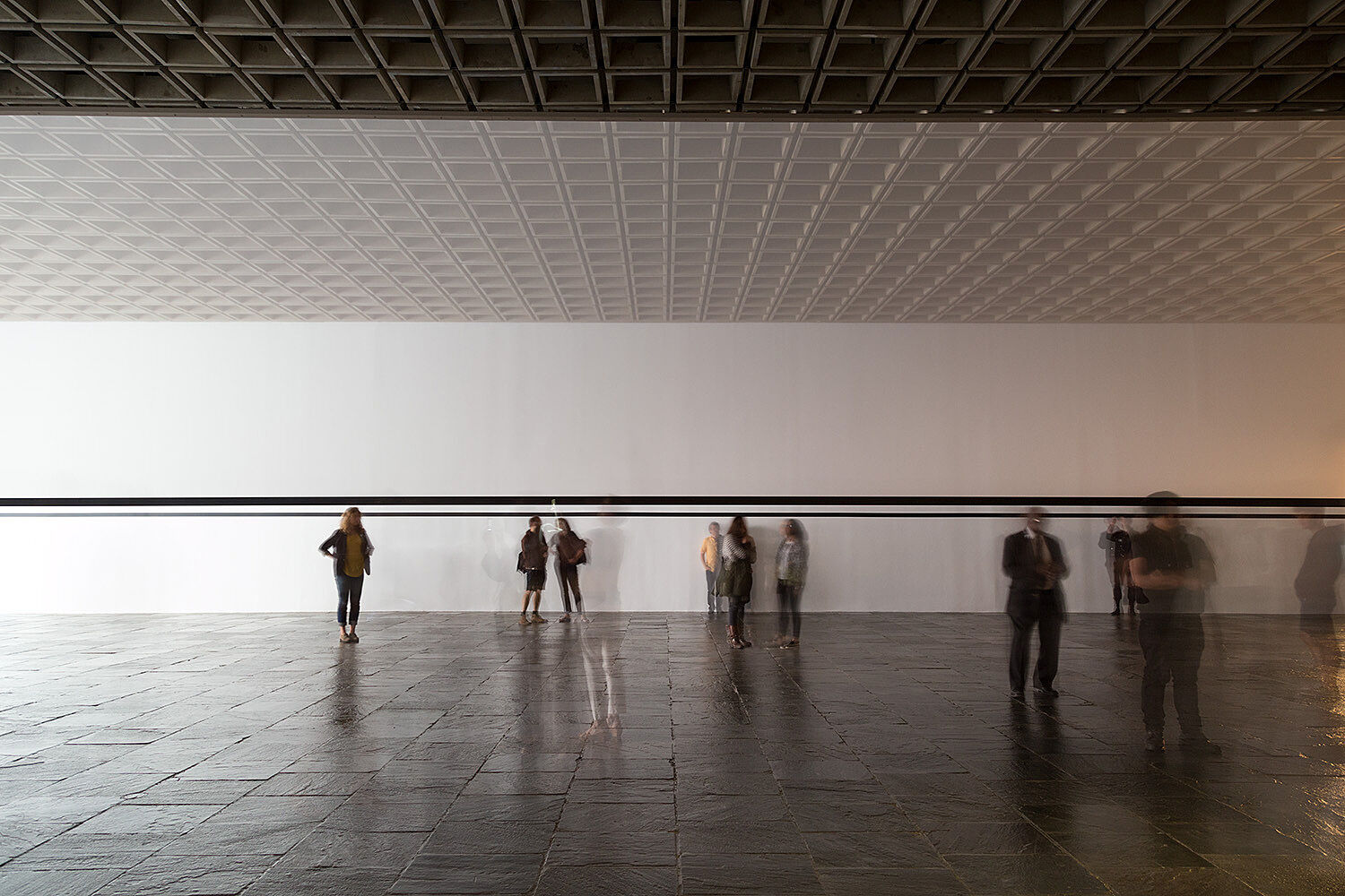 Blurred image of people standing in a gallery.