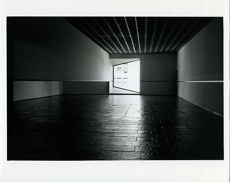 Long view of a darkened gallery with a window at the end of the room.