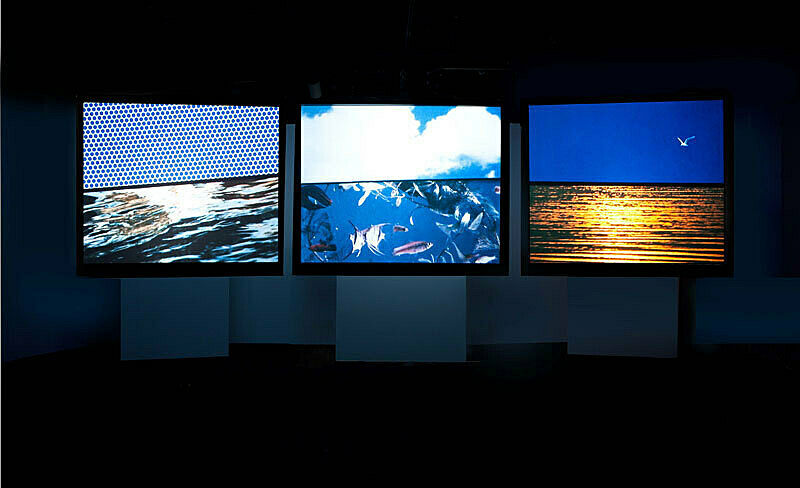 Installation view of three screens in a darkened gallery.