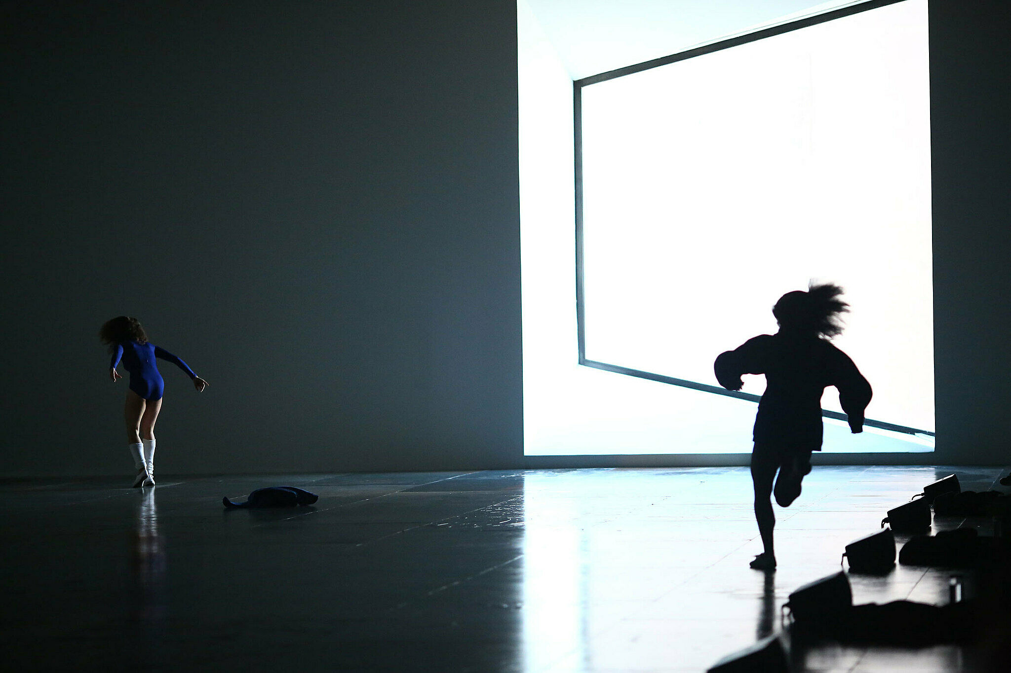 A dancer in blue makes a move while another one runs around the gallery.