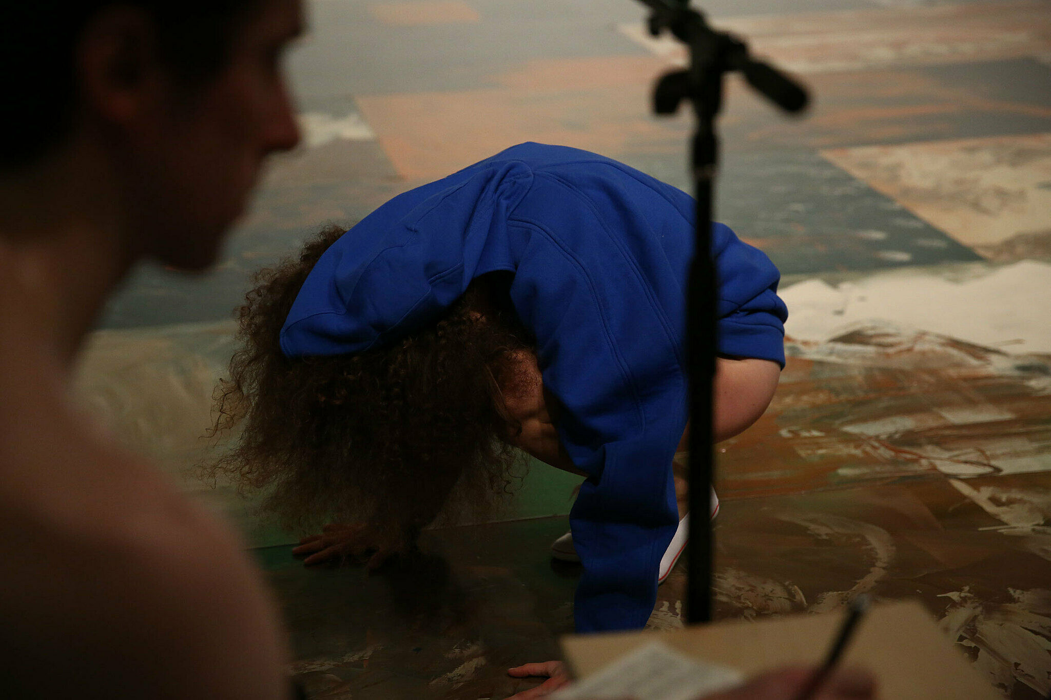A dancer dressed in blue hunches over on the floor.