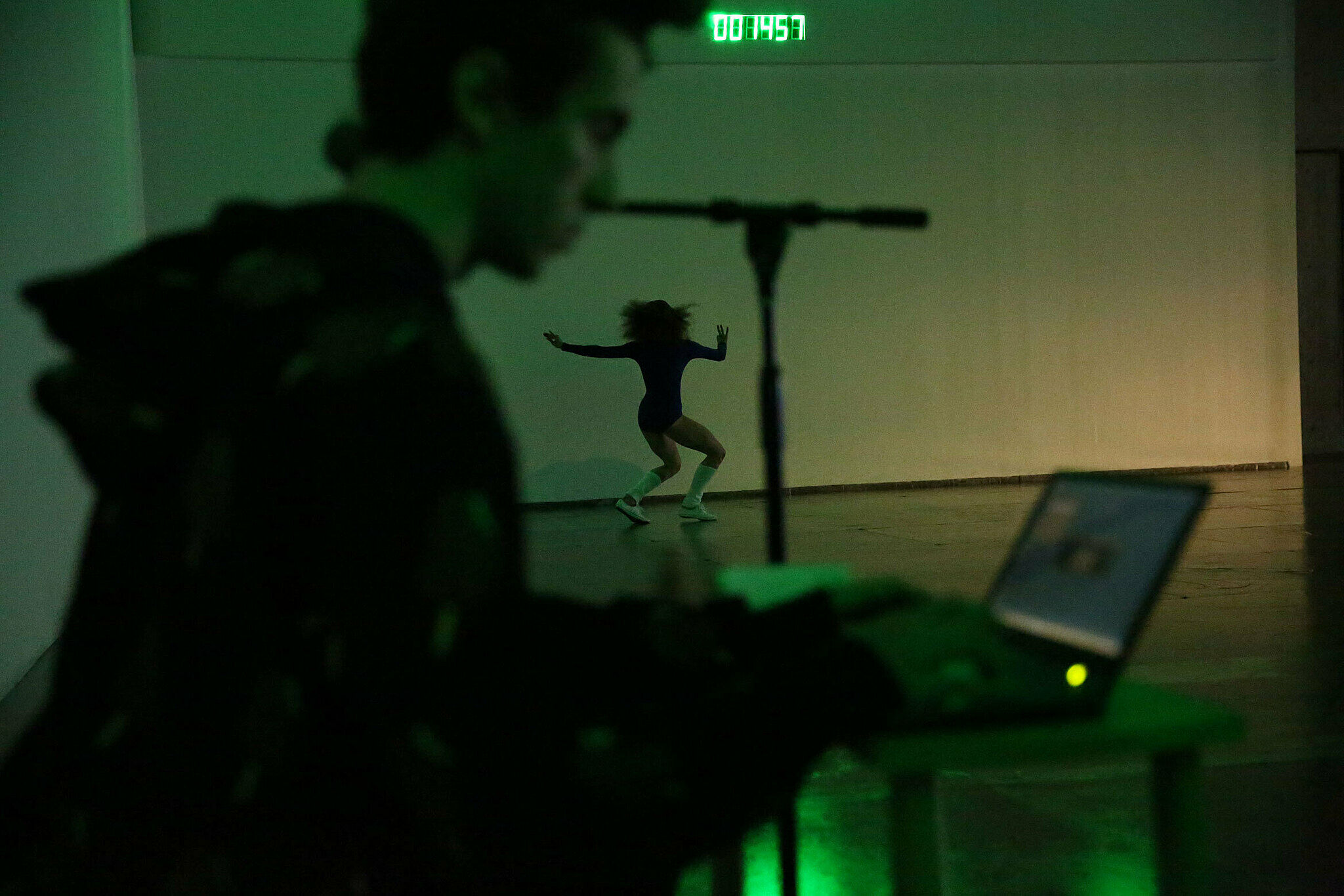 A man on a laptop sits in the foreground while a woman dances in the background.