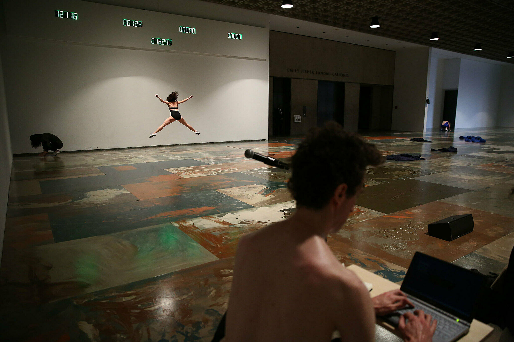 A dancer jumps in the background while a man sits in front of a laptop in a gallery.