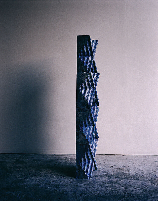 A tall sculpture with criss-cross shapes and shades of blue.