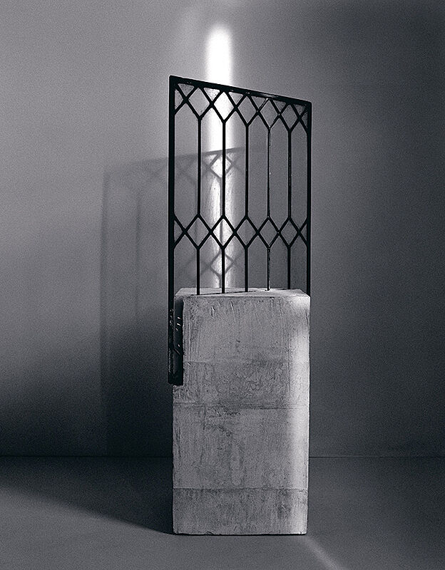 A sculpture with a black frame inserted into a concrete block.