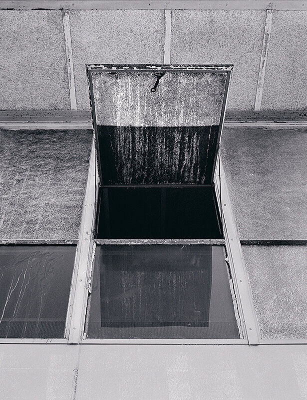 A window pane propped open on a roof.