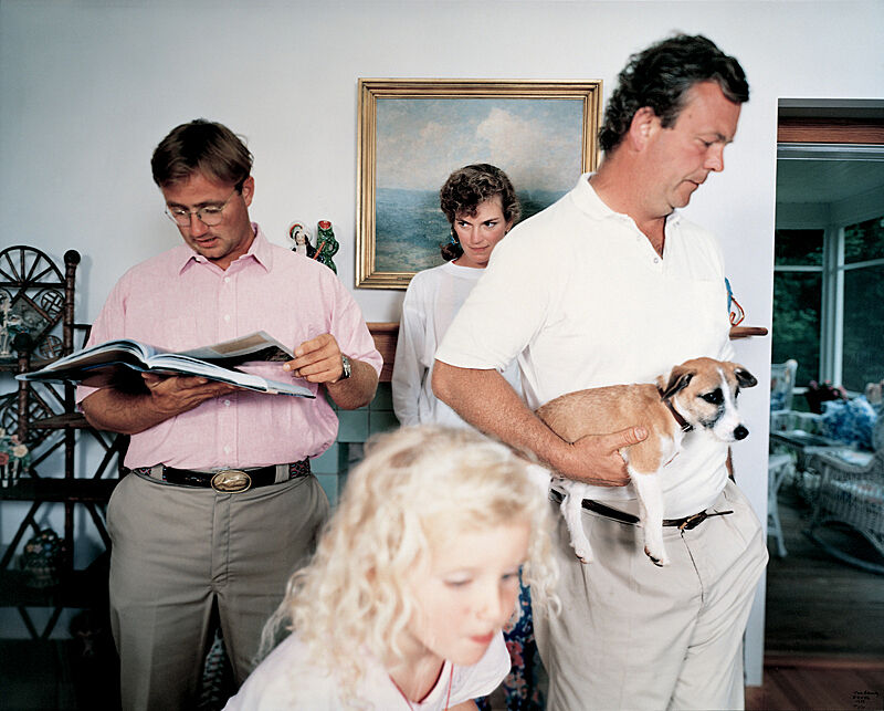 Photo of a man with a dog and a man reading, a girl and a woman in a room.