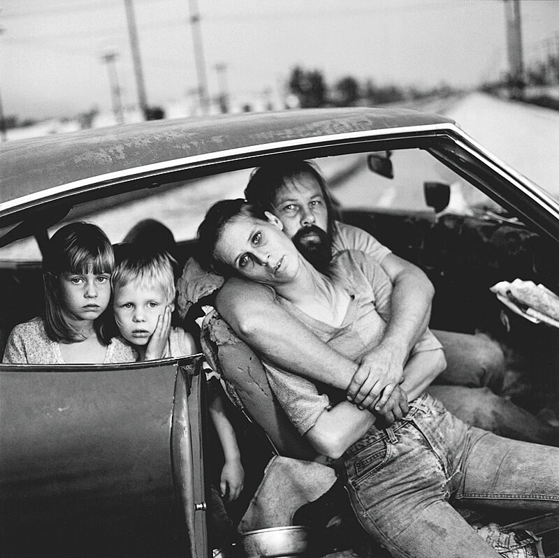 Family sits in a car in a black and white photo.