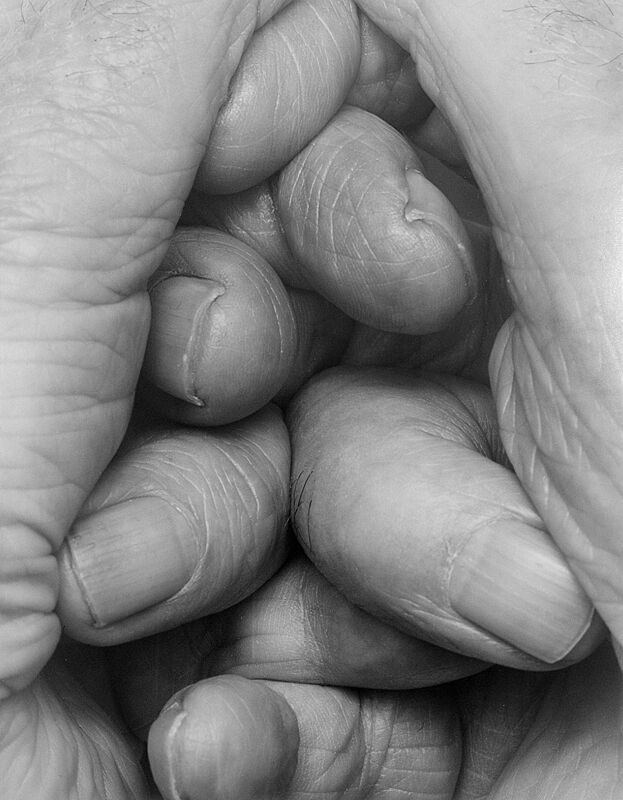 Fingers interlocked in a black and white photo.