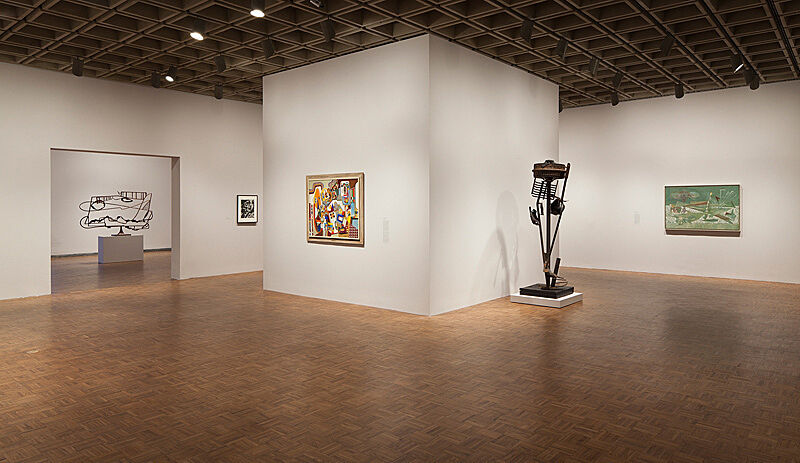 An installation view in a gallery with wooden floors and white walls.