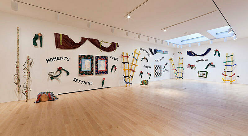 An art installation featuring curtains, rope ladders, text, and more on the walls.
