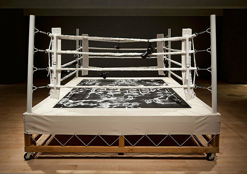 A diorama of a boxing ring with white ropes around it.