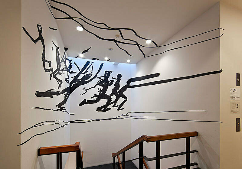 Artwork of running people on a white wall.