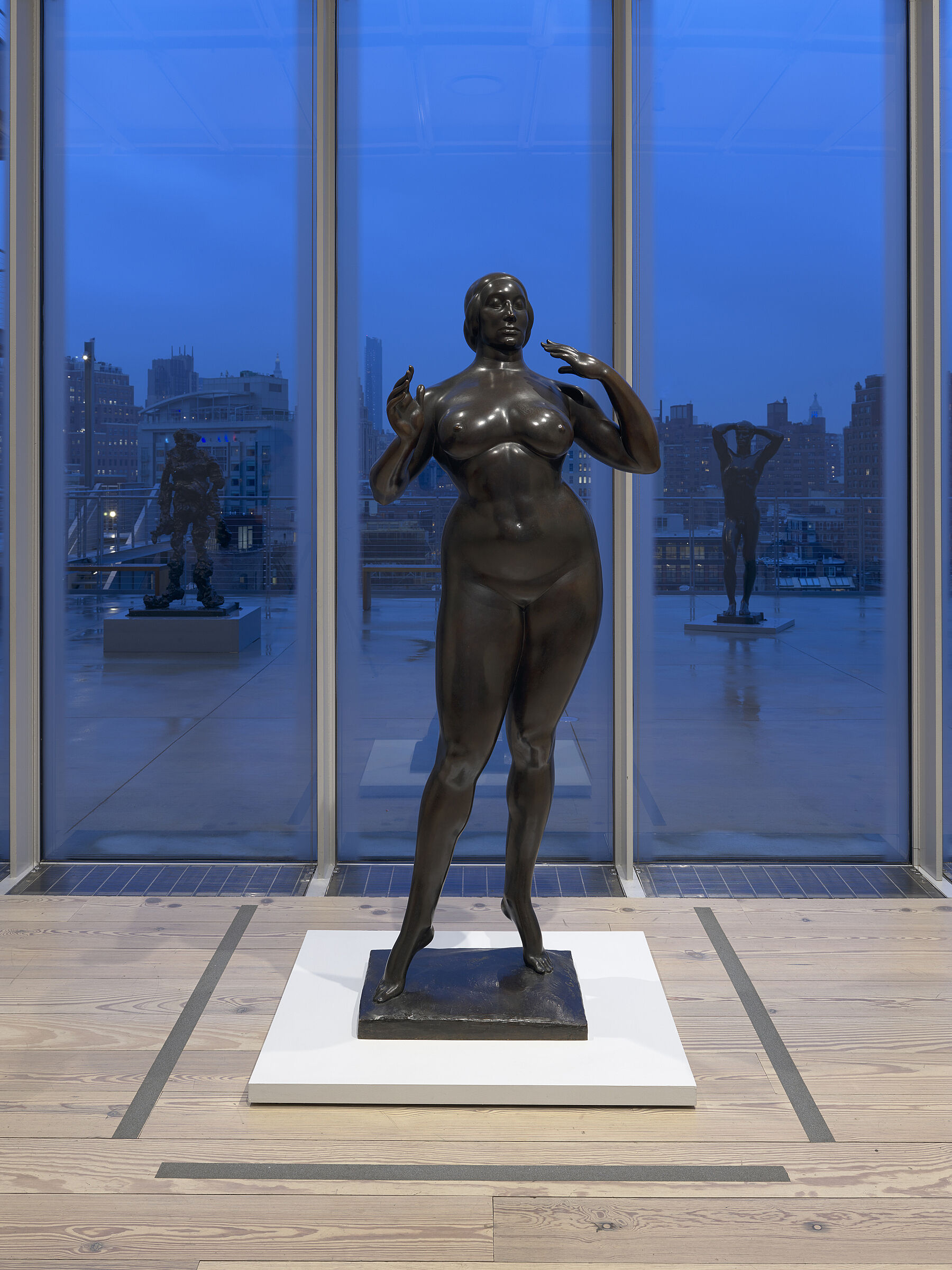 Statue of a women standing in front of window at the Whitney.