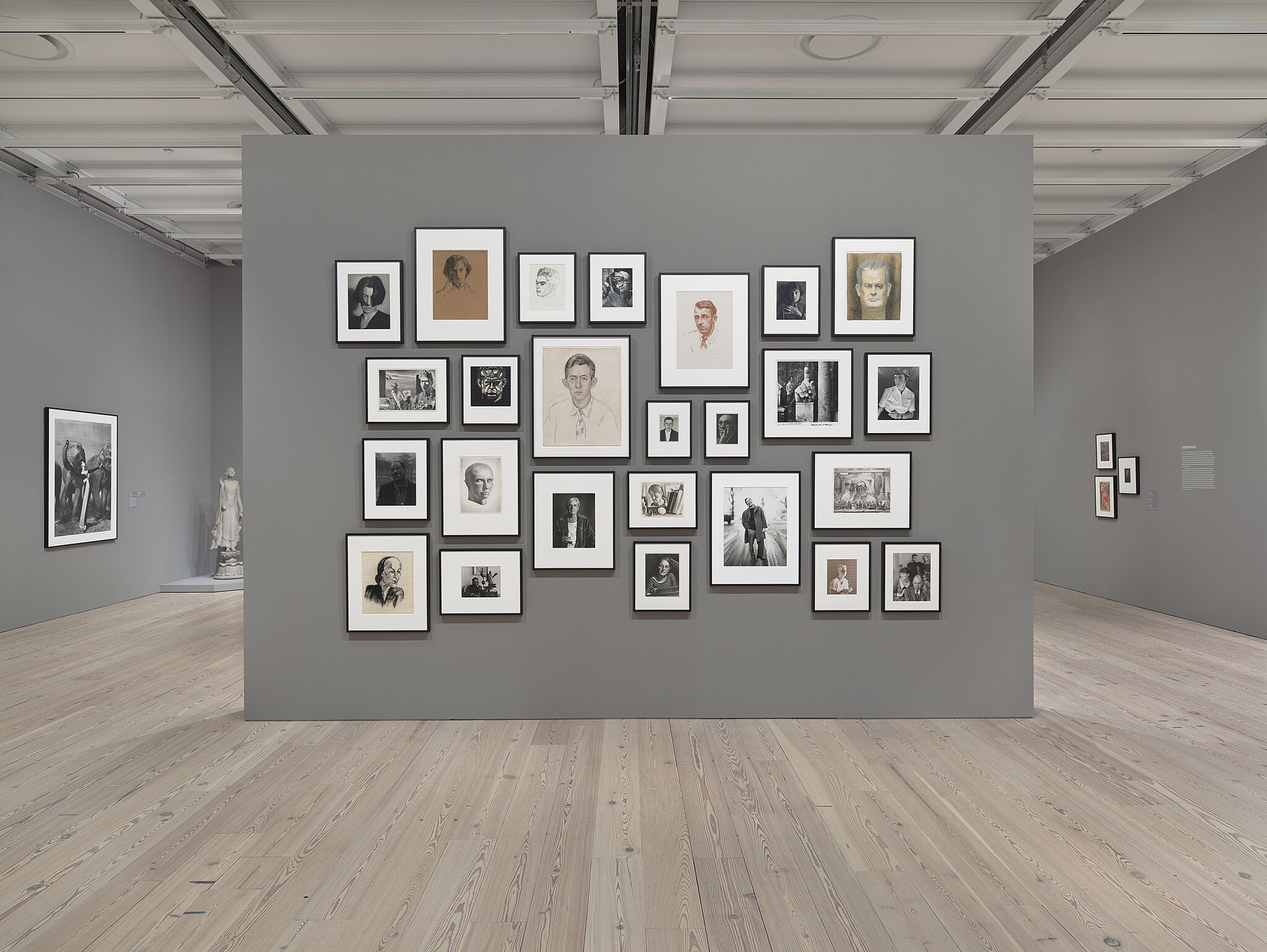 Freestanding wall in the middle of the gallery holds multiple images.