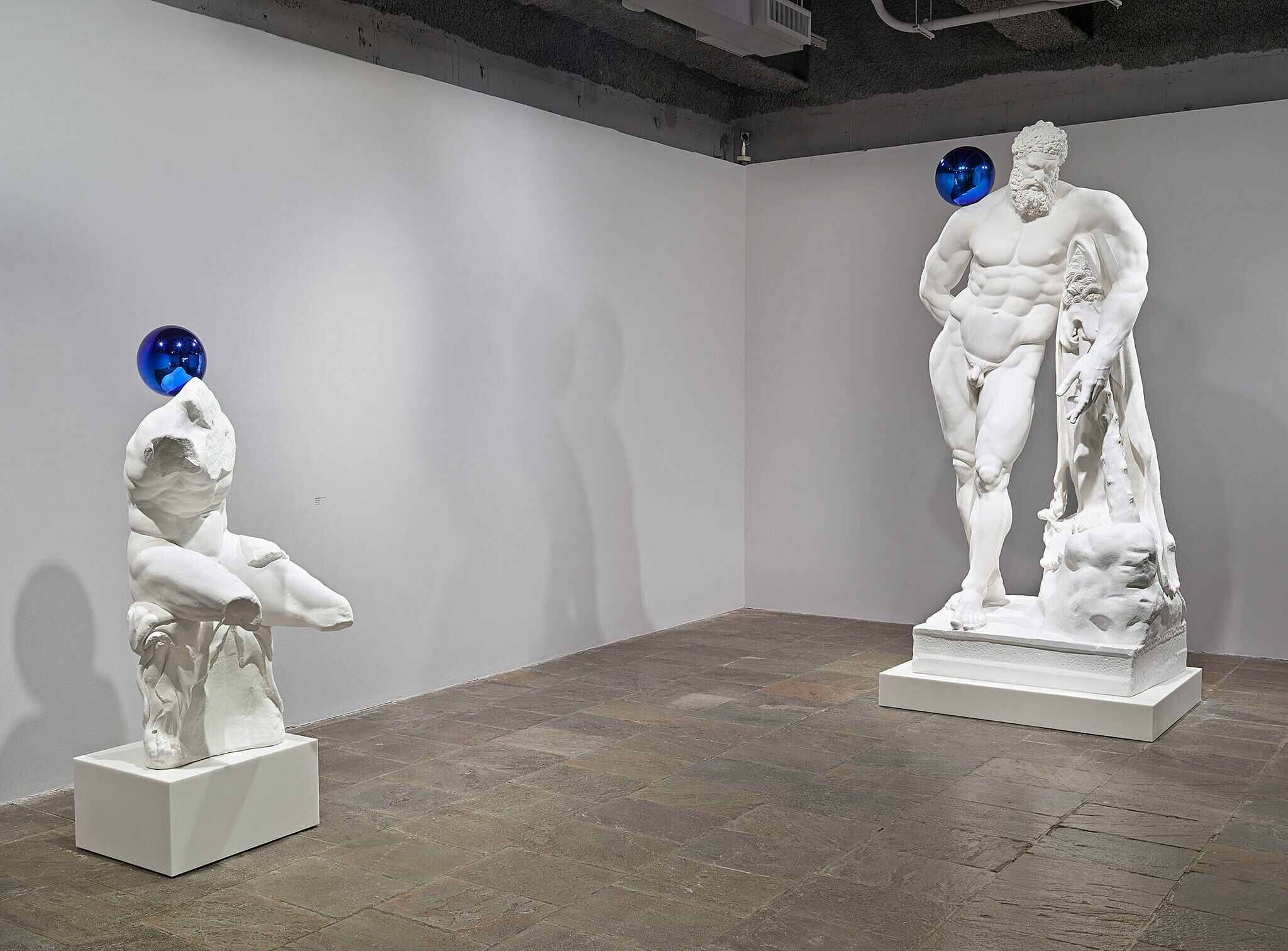 Two Koons statues with a blue ball balanced on their shoulders.