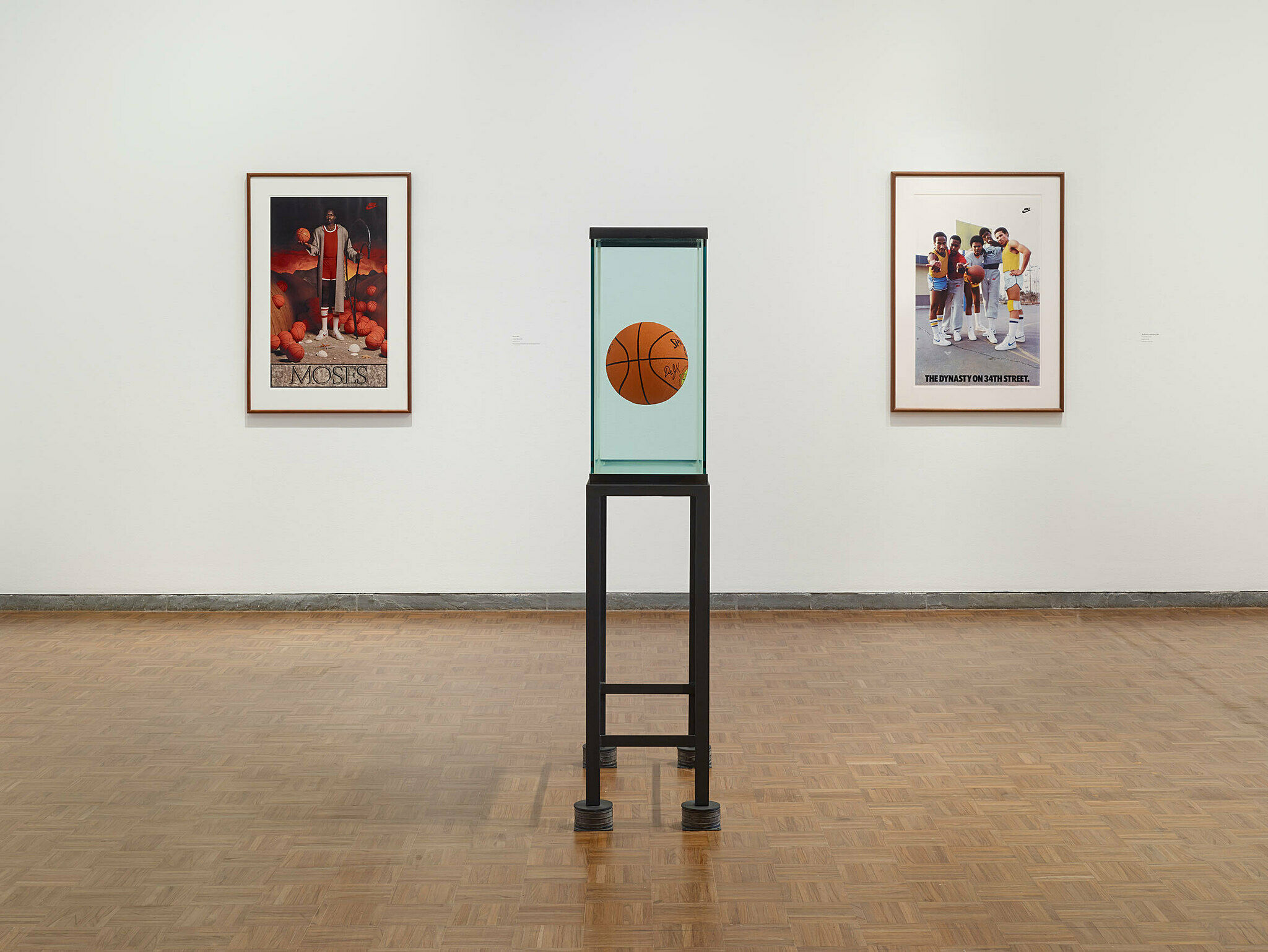 Basketball suspended in liquid with paintings behind it.