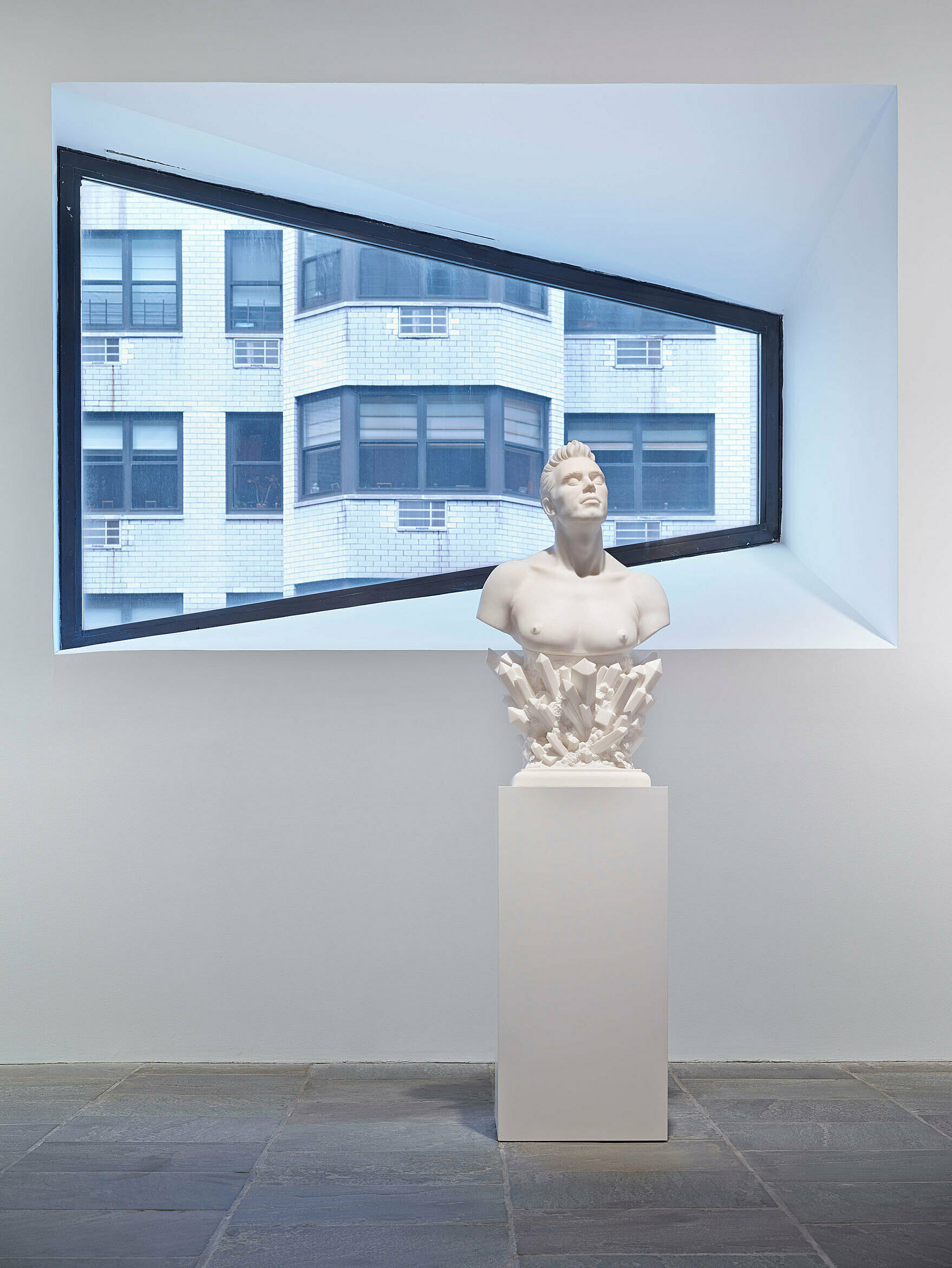 Bust of a man in front of window at the Whitney.