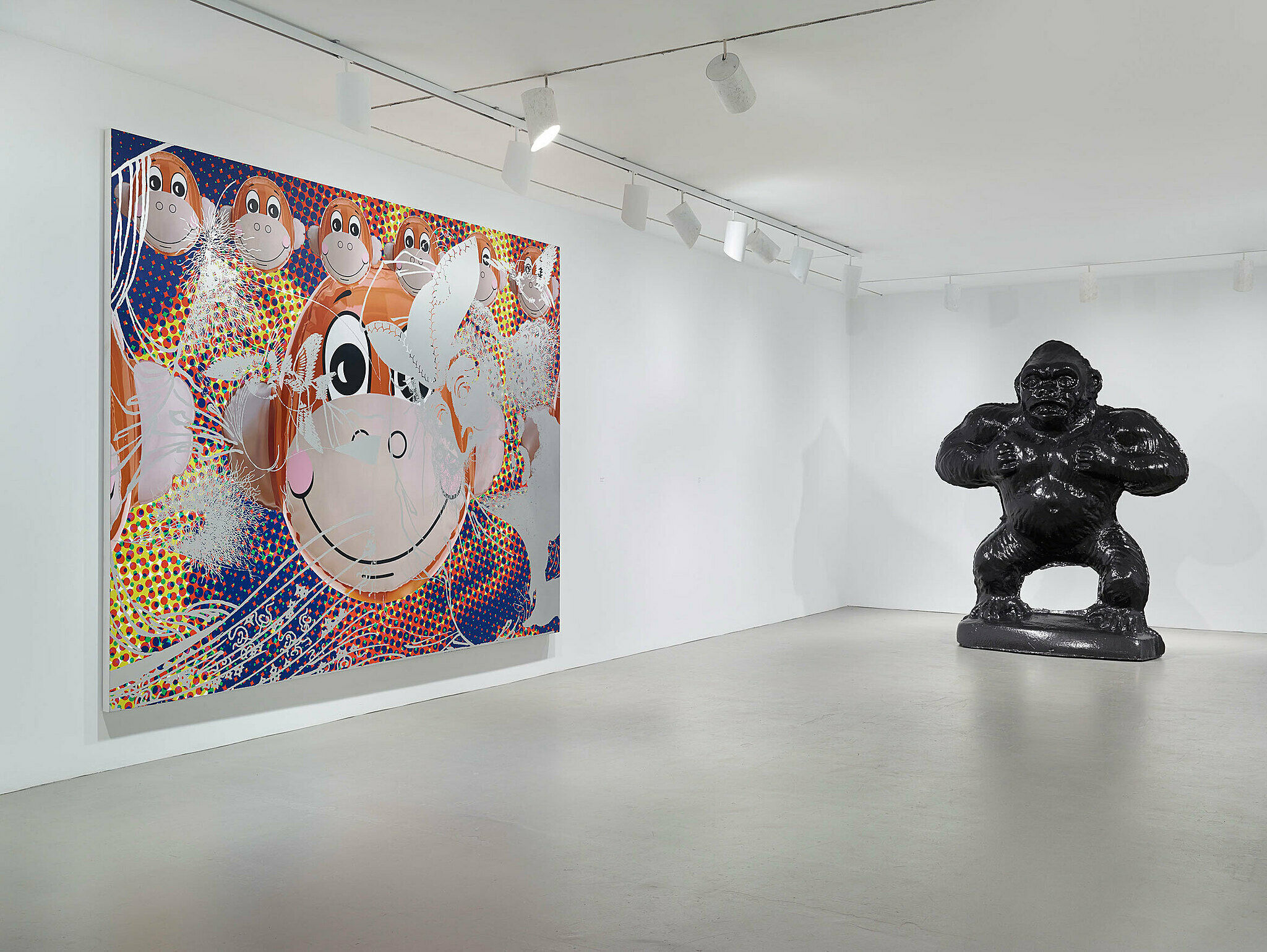 Gorilla statue stands next to large painting.