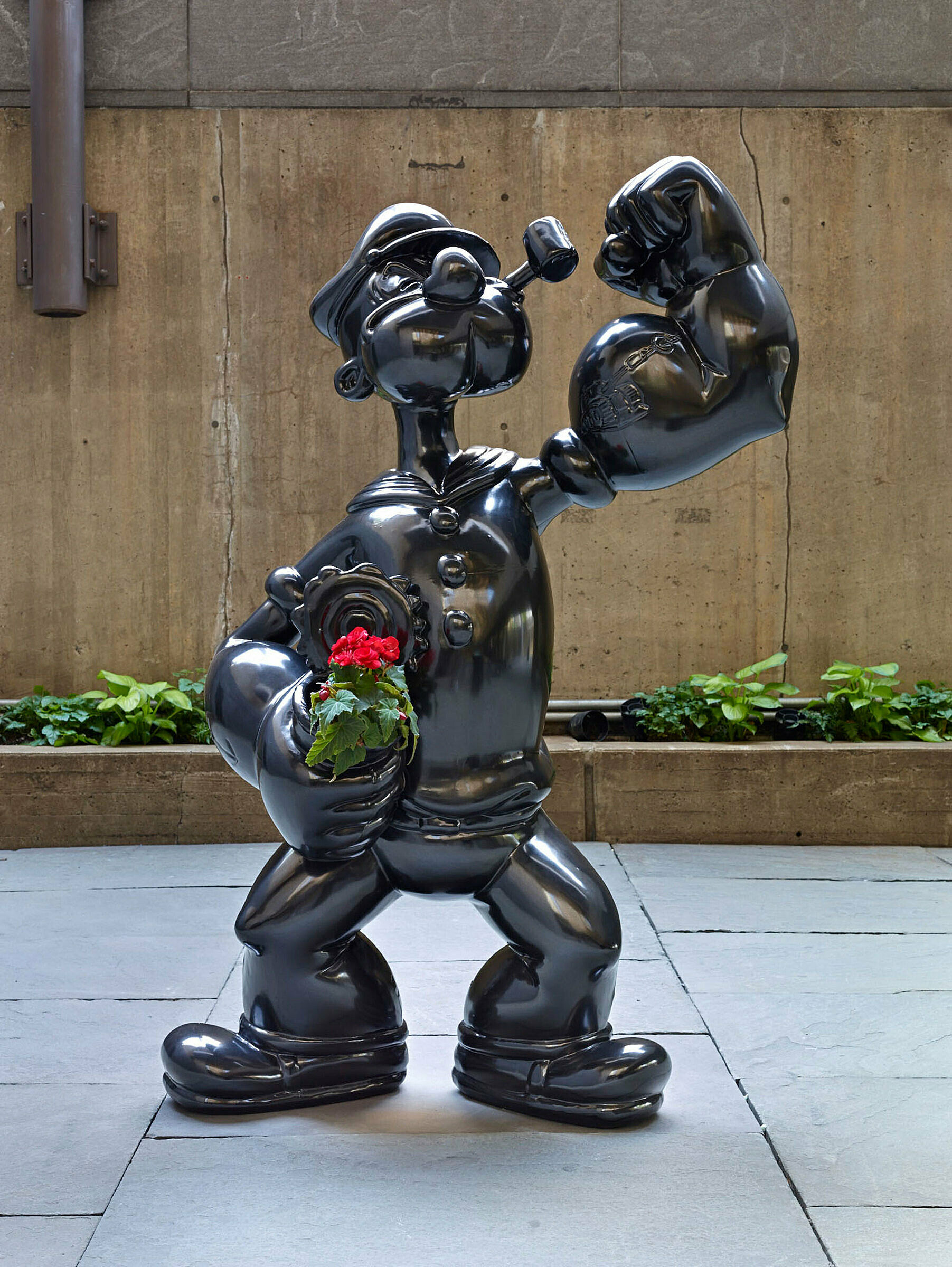 Popeye statue holding flowers.