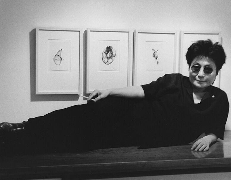 Yoko Ono reclining in front of artwork.