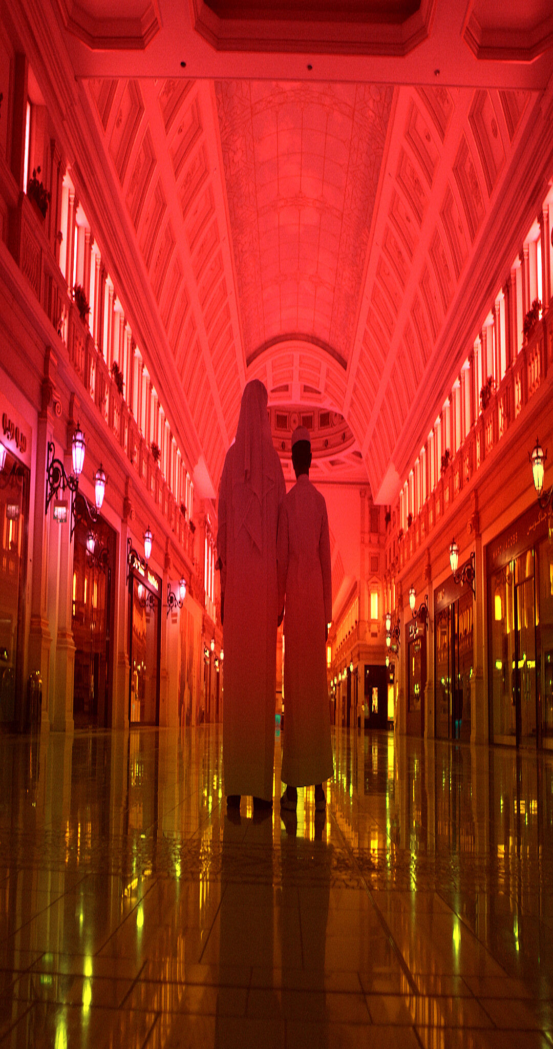 A video still by Sophia Al Maria of two people walking down a red hallway.