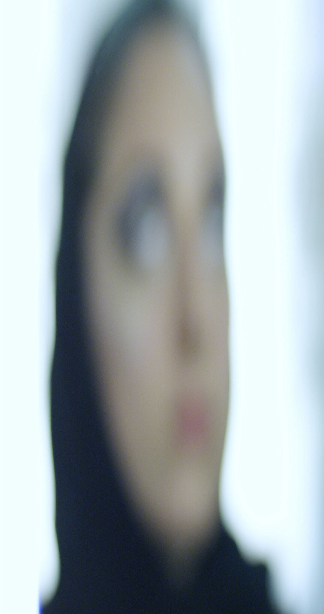 A video still by Sophia Al Maria of a blurred woman's face.