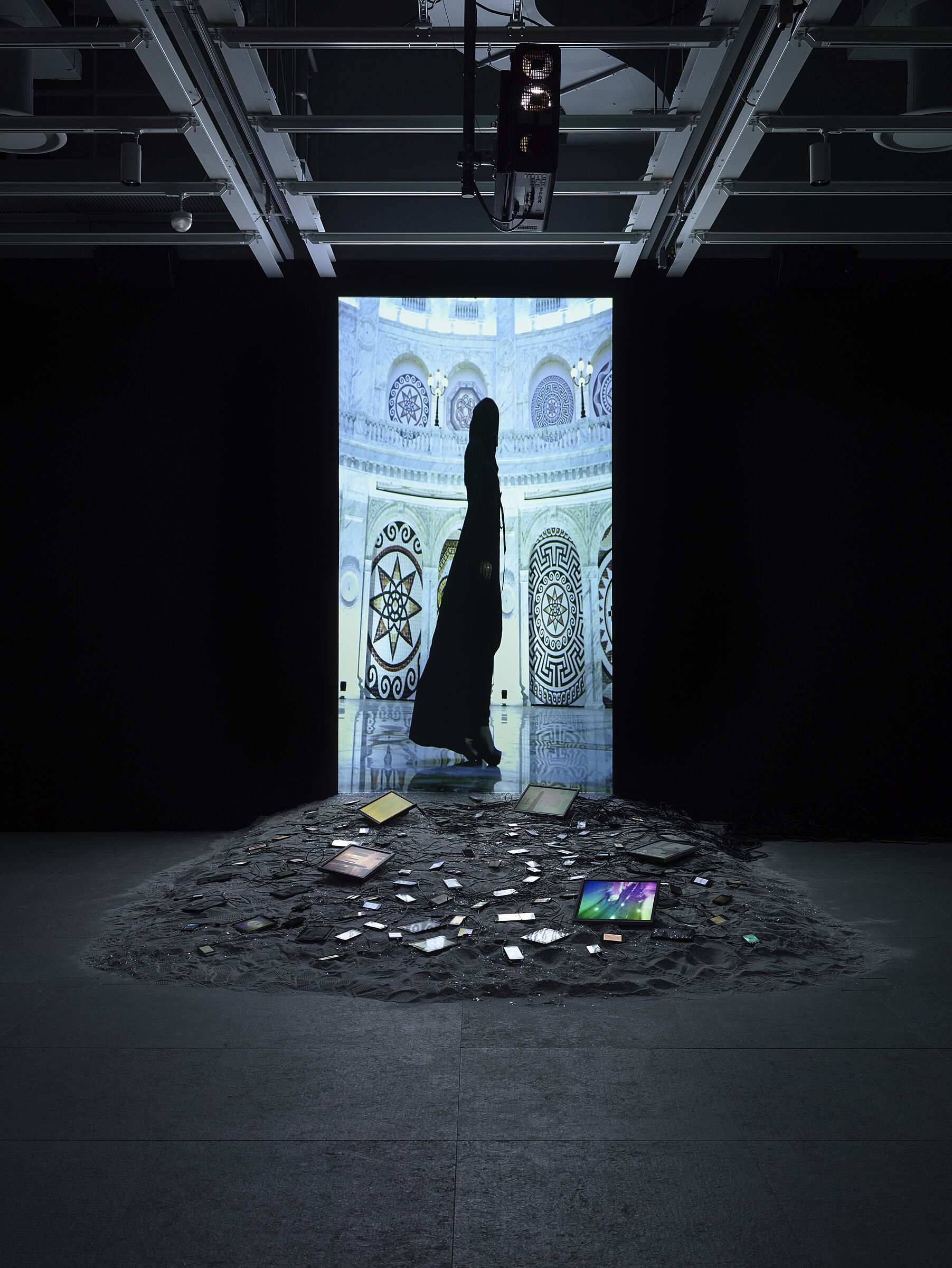 Video installation by Sophia Al-Maria with a black image of a woman standing on screen.