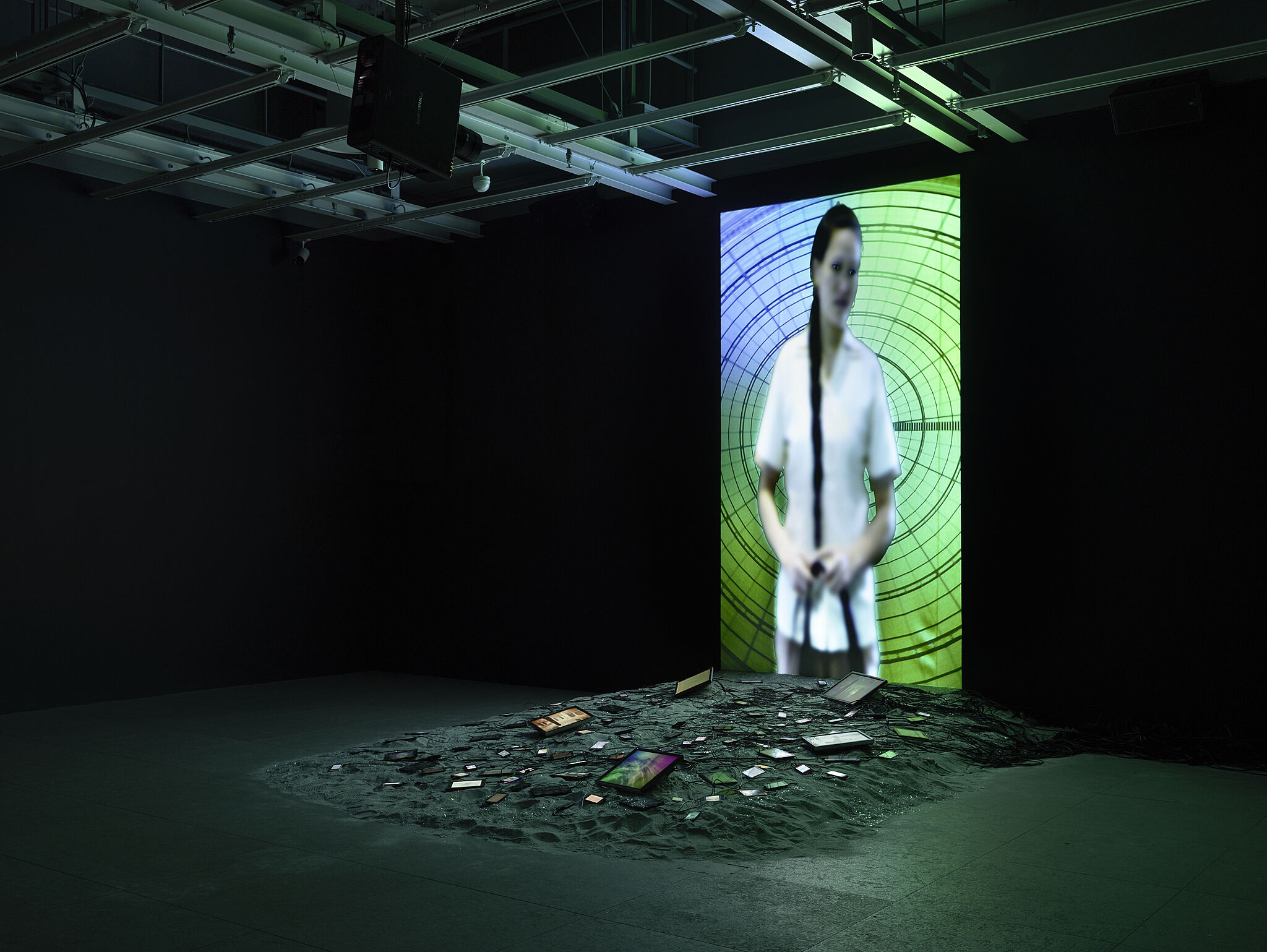 Video installation by Sophia Al-Maria with an image of a woman on a blue and green screen.