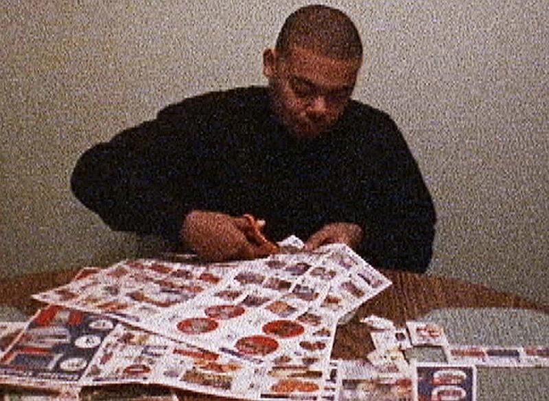 Man cutting through coupons.
