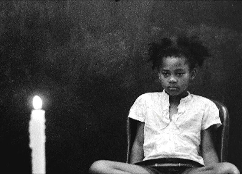 Girl sitting in a chair in front of a candle.