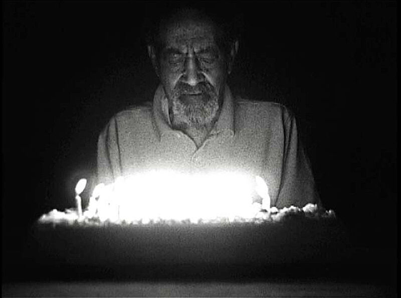 Man illuminated by birthday cake candles.