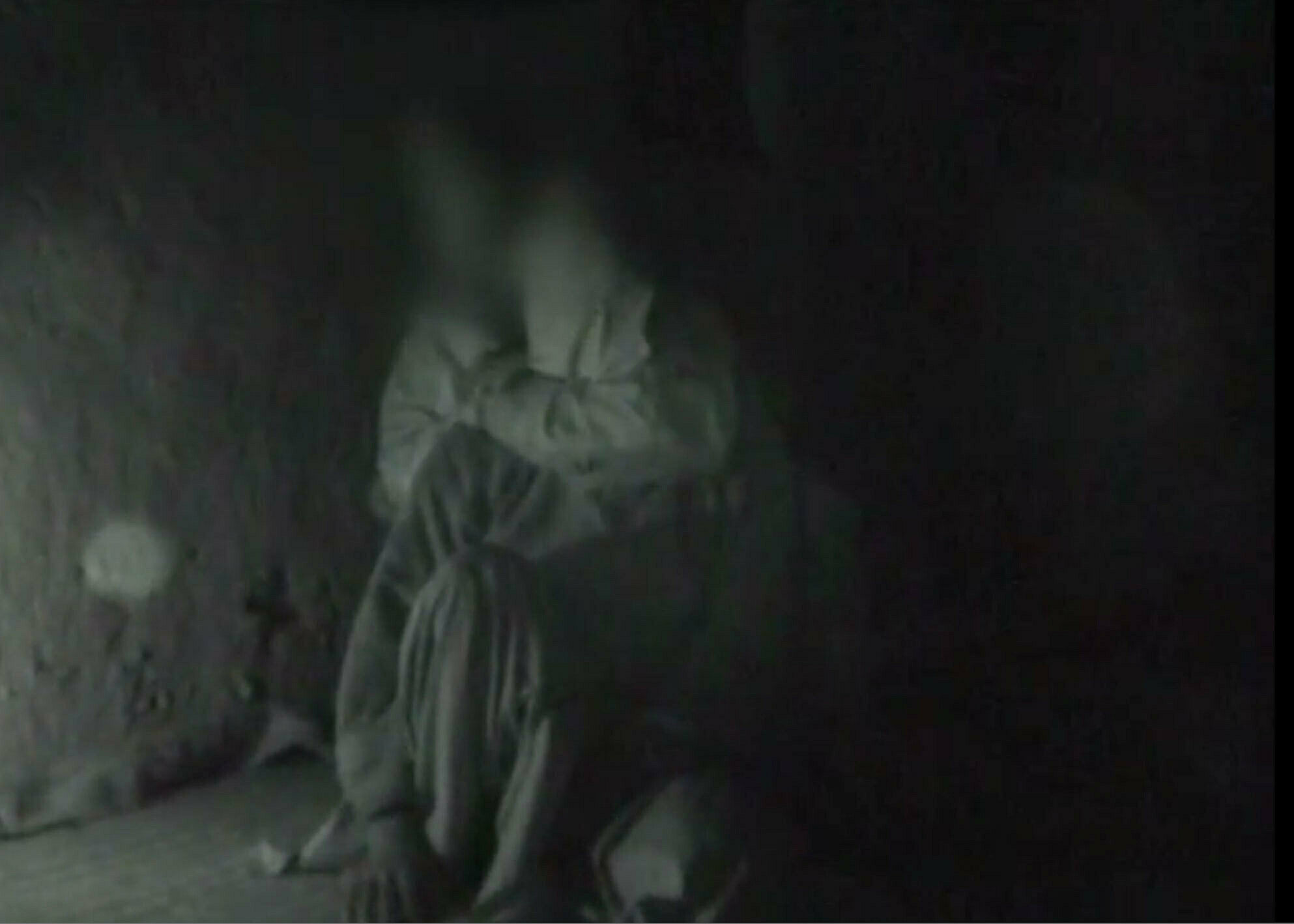 Blurry and dark image of a person sitting.