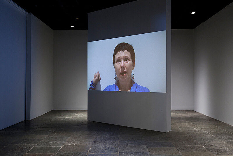 A video installation with a screen featuring a woman's face.