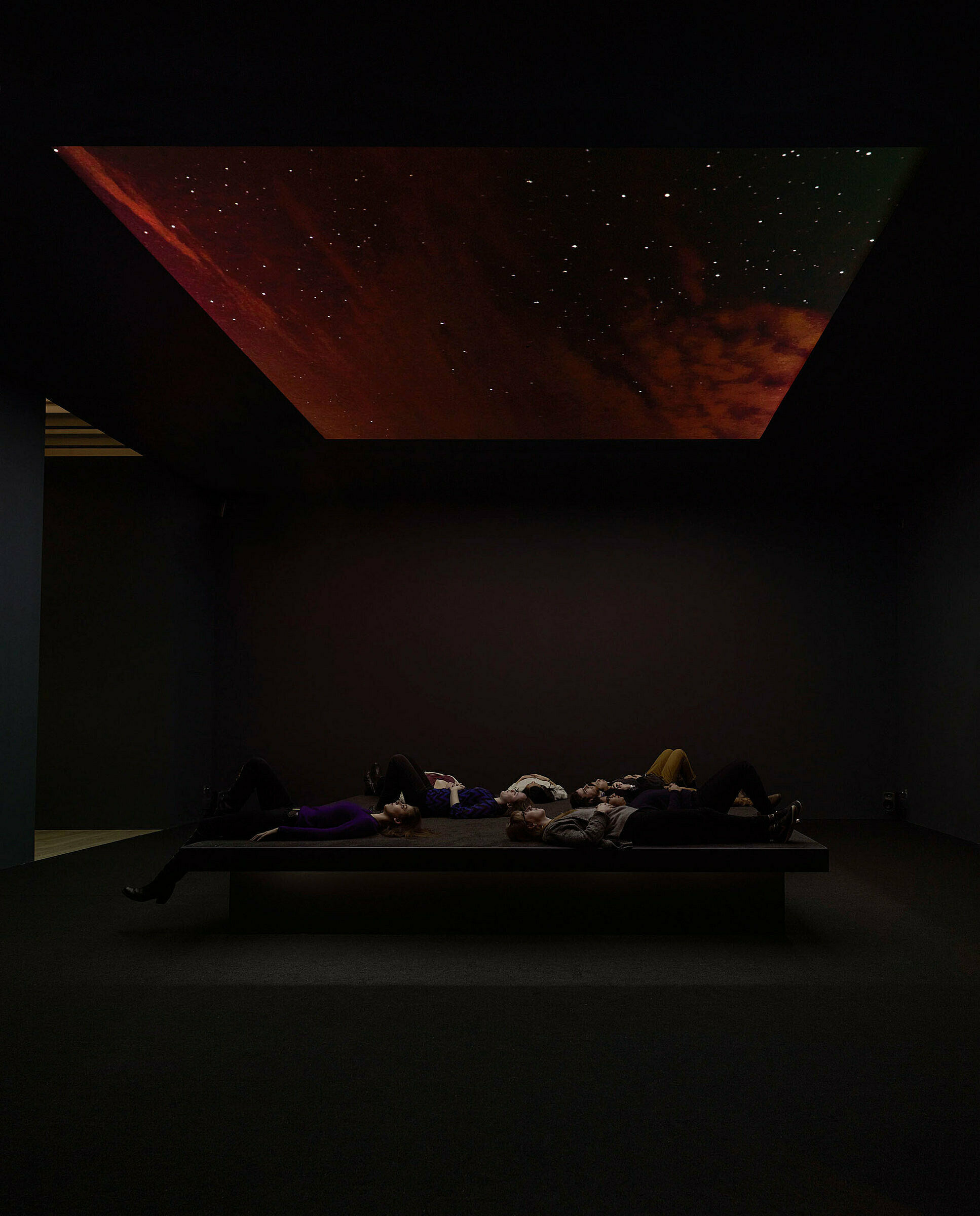 Visitors laying down looking at red clouded solor system projection.