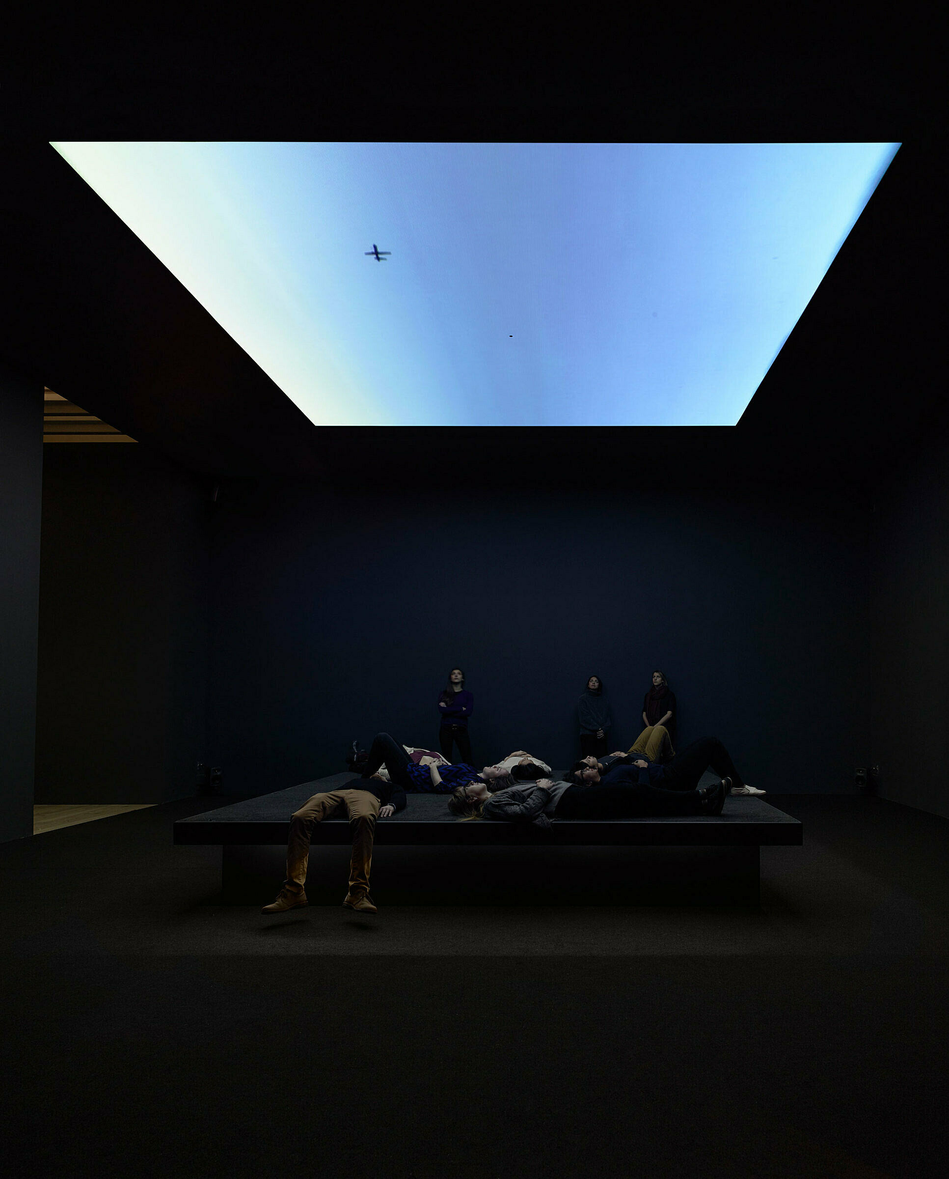 Visitors laying down looking at blue gradient projection.