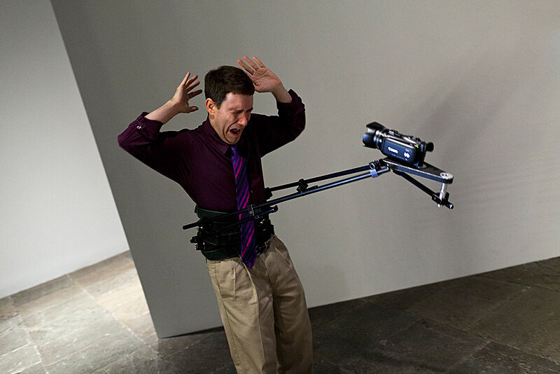 An actor holds his hands in the air with a video camera attached to his body in an art installation by Xavier Cha.