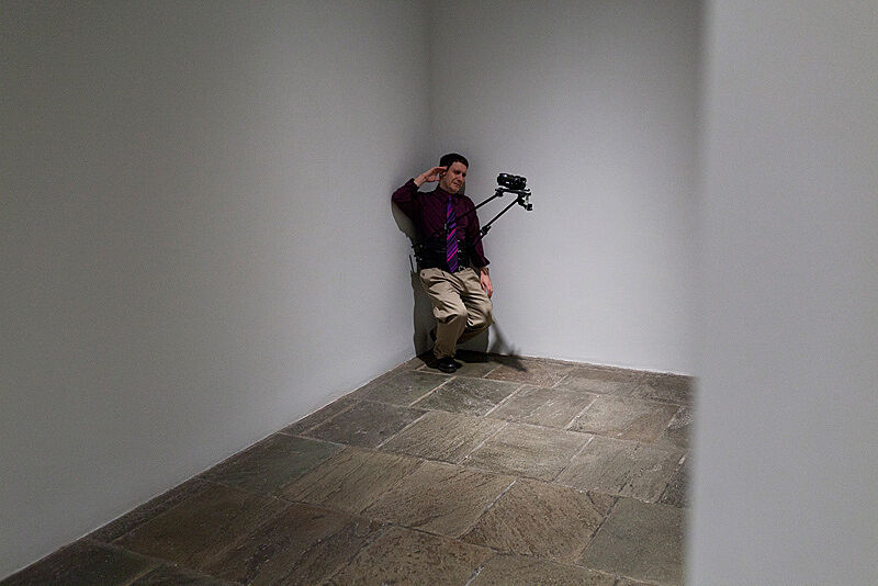 A man leans in the corner of an art gallery with a video camera attached to him.