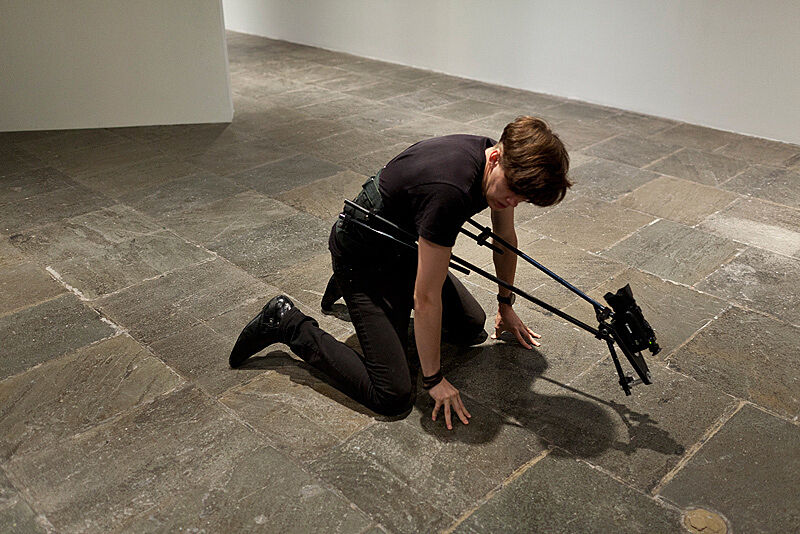 A man kneels down on a gallery floor with a video camera attached to his body.