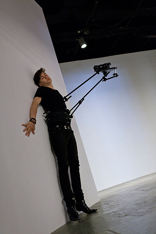 A man leans flat up against a white wall in an art gallery with a video camera attached to his body.