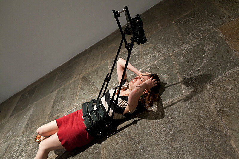 A woman lies on the ground with her hands on her head and a video camera attached to her body.