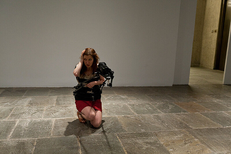 A woman kneels on the floor of an art gallery with a video camera attached to her body.