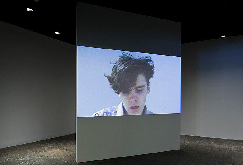 A video installation of a person's head on a large screen in the gallery.