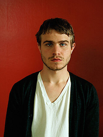 A headshot of actor Brady Corbet wearing a white v neck t shirt and black sweater.