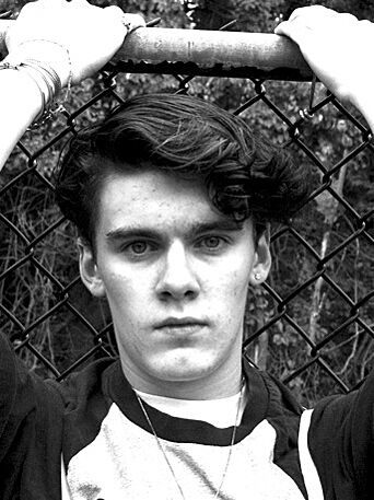 A black and white headshot of actor Eamon James with hands above his head holding onto a fence.