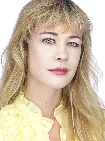 Head shot of actress Michal Sinnott wearing a yellow blouse.