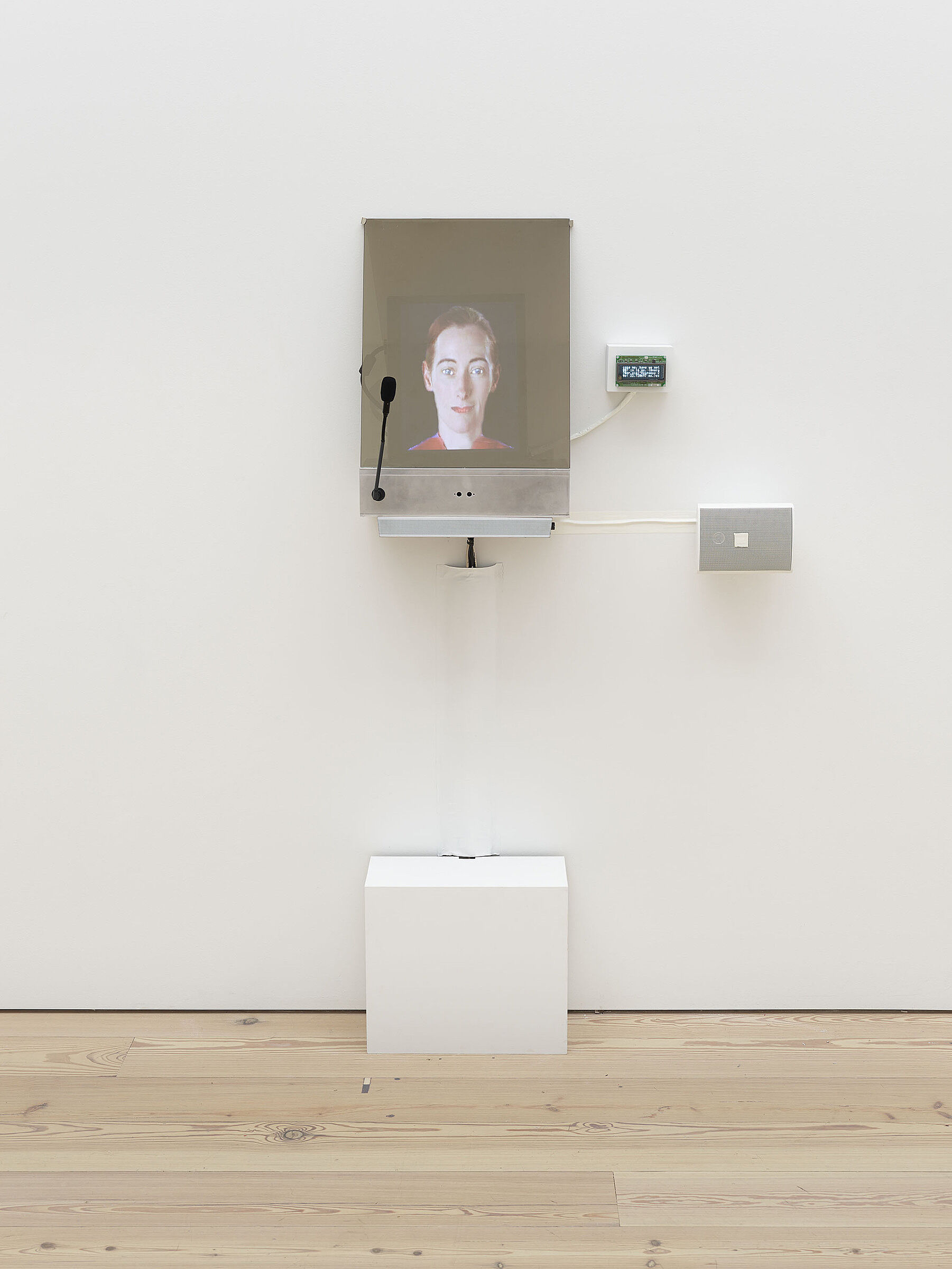 A small video screen on a gallery wall projecting a person's face.
