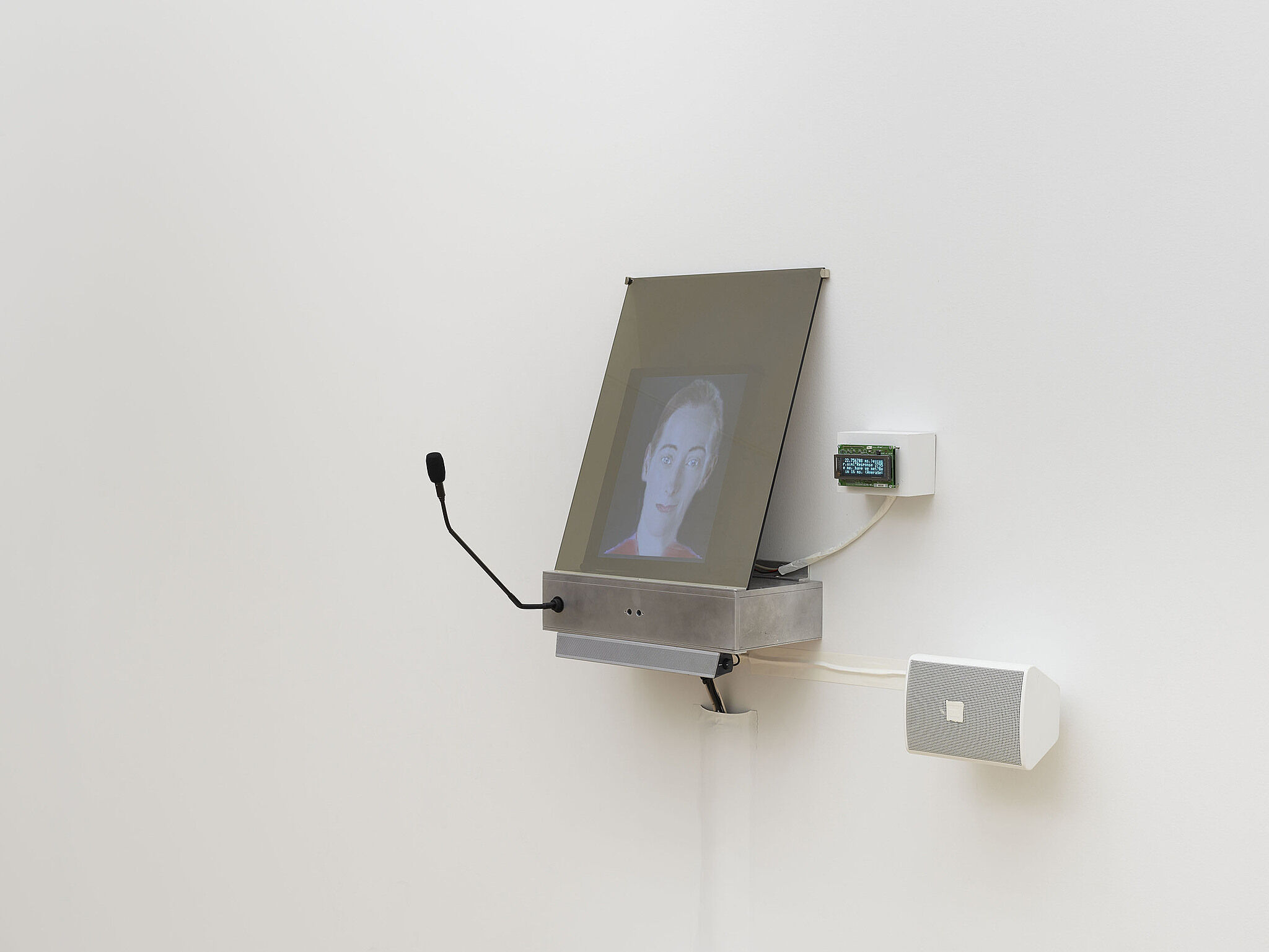 A small video screen on the wall projecting a person's face.